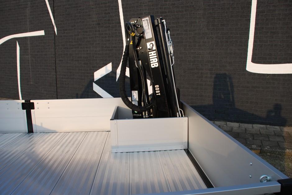 Bestelwagen met open laadbak en laadkraan